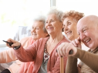 Group of elderly people laughing and smiling watching TV