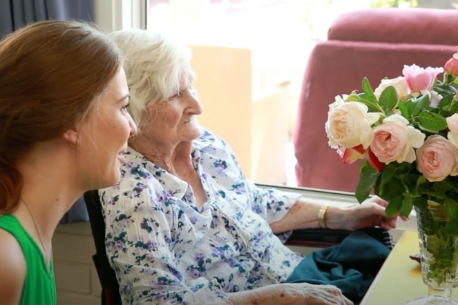 Elderly Lady with Carer Looking at Flowers